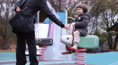 Mather with Little  girl in  Kids playground seesaw having fun in Autumn  time Stock Footage