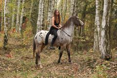 young girl with appaloosa horse in autumn - stock photo