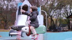 Mather with Little  girl in  Kids playground having fun  in Autumn Fall time Stock Footage