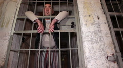 Prisoner standing behind his prison cell door Stock Footage
