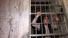 Rebellious prisoner show his middle finger from behind his cell bars Stock Footage