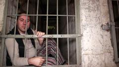 Hopeless man behind his cell bars Stock Footage