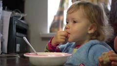 Two year old child girl eats with fingers in front of the computer with cartoons - stock footage