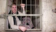 A man sitting on the ground laughs from behind his prison cell door Stock Footage