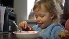 Two year old child girl eats with fingers in front of the computer with cartoons Stock Footage