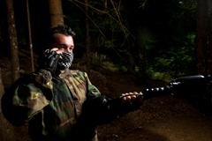 Paintball player calling someone at the phone - stock photo