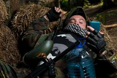Paintball player resting and looking at the phone - stock photo