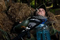 Paintball player resting and smoking a cigar - stock photo