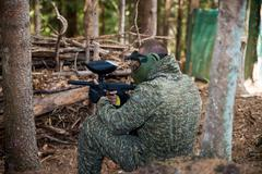 Paintball Players Hide Behind Tree - stock photo