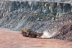earth mover driving around in a surface mine quarry - stock photo
