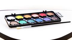 Box of watercolors on a white table brightly lit - stock photo