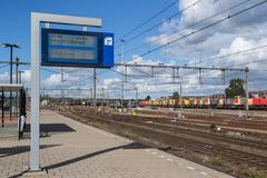 notice board with departure times at dutch railway station - stock photo