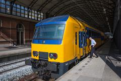 conductor getting in a train ready to start in the hague, the netherlands - stock photo