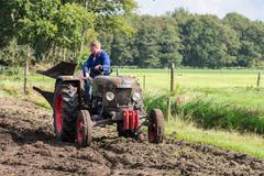 Farmer riding with an old tractor during a dutch agricultural festival Stock Photos