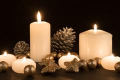 burning candles with pine apples and gilded stars on a black background - stock photo