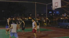 Taiwanese man play night basketball - finish play with jumpshot Stock Footage