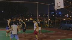 Taiwanese man play night basketball - finish play with jumpshot - stock footage