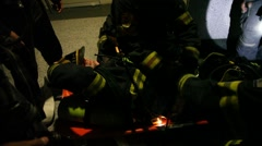Firefighters treat and evacuate injured victim from highrise building - stock footage