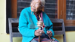 Old woman with hand held Prayer Wheel, Nepal Stock Footage