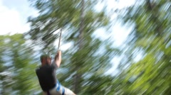 Two Men Fly Past Camera on Zip Lines Stock Footage