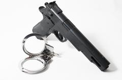 Weapon crime concept gun and handcuffs Stock Photos