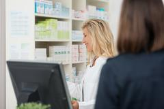Female pharmacist dispensing medicine to a patient Stock Photos