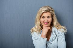 attractive mature woman on gray wall background - stock photo