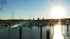 2599 Boat Dock at Sunset with Sun Flare Over Bridge, 4K Stock Footage