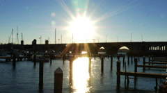 2601 Boat Dock at Sunset with Sun Flare Over Bridge, 4K Stock Footage