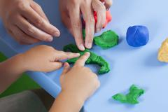 child and mother playing with playdough - stock photo