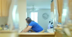 Young woman putting dishes/glasses in kitchen cupboard. Ultra HD 4K - stock footage