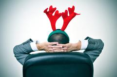 man with a reindeer antlers headband in his office chair - stock photo