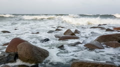 Waves and foam on rocky beach Stock Footage
