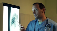 Male doctor looking on lungs xray and  talking to the camera  in hospital   HD Stock Footage