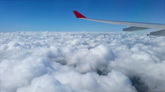 Airplane flying above the clouds on a sunny day Stock Footage
