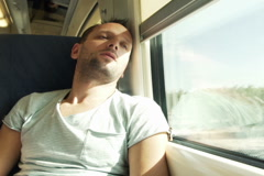 Young sad man sitting in the train and looking through the window  NTSC Stock Footage