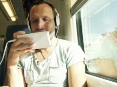 Young man watching funny movie while sitting in train NTSC - stock footage