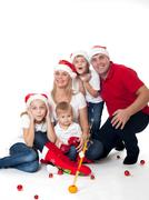 Happy cute family in santa's hats Stock Photos