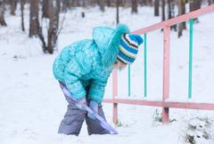 Happy kid girl child outdoors in winter digging snow with toy spade Stock Photos