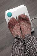 Feet with wool socks and electric heater Stock Photos