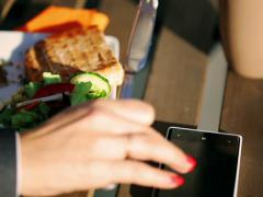 Businesswoman eating lunch and typing message on cellphone outside the cafe Stock Footage