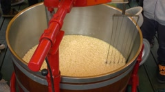 Stirring during Gouda cheese making at the cheese market in Gouda, Netherlands. - stock footage