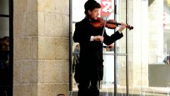 Street violinist in religious clothing on Mamilla Street in West Jerusalem Stock Footage