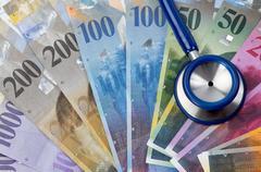 swiss francs and stethoscope - stock photo