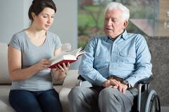 senior care assistant reading book - stock photo