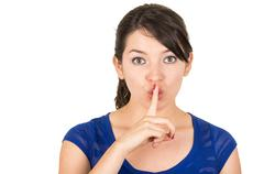 beautiful young woman gesturing silence shhh with finger on mouth - stock photo