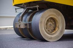 Wheels of steam roller pressing asphalt on the road Kuvituskuvat