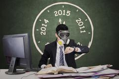 Worker wearing gas mask and looking timepiece Stock Photos