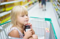 Adorable girl sit with set of good in shopping cart in supermarket Stock Photos