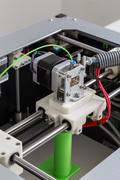 3d printer with bright green filament - stock photo